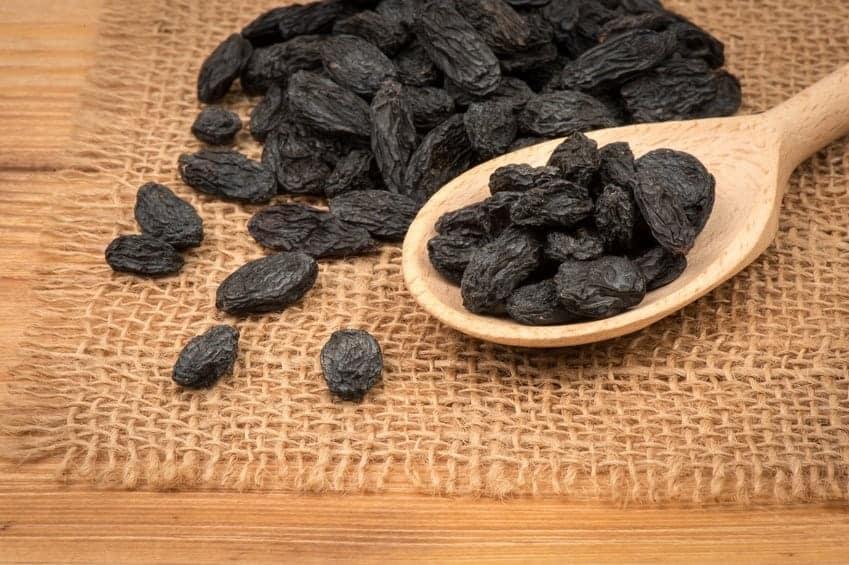 Black Raisins on the Wooden Background.