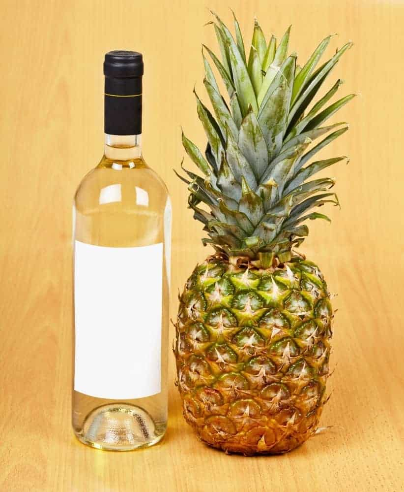 Bottle of white wine and large pineapple