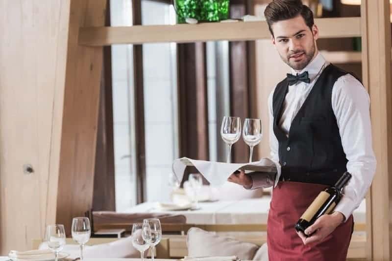 waiter holding wineglasses and bottle